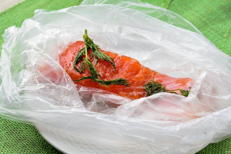 Через каждые 4-5 часов слегка встряхивайте и переворачивайте пакет, чтобы семга лучше засолилась. В конце второго дня рыба будет полностью готова, уберите укроп, он больше не понадобится.