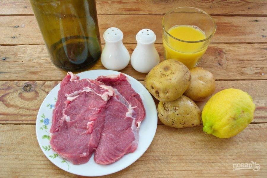 Для приготовления блюда возьмите говядину, картофель, сыр твердый, соль, специи, растительное масло, апельсиновый сок, лимон.