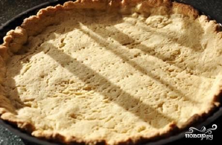 3. Выложите тесто в жаропрочную форму, распределите руками так, чтобы получились бортики. Вилкой сделайте проколы. Сверху выложите лист пергамента и какой-нибудь утяжелитель: горох, крупу, фасоль. Отправьте в разогретую духовку минут на 10-12, а затем уберите утяжелитель и запекайте до румяной корочки еще минут 15.