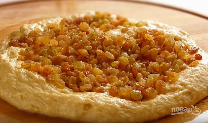 7. Помытый и подсушенный изюм добавьте в тесто и месите, чтобы он равномерно распределился. Готовое тесто переложите в миску, накройте полотенцем или пленкой и оставьте в теплом месте на 1.5 часа.