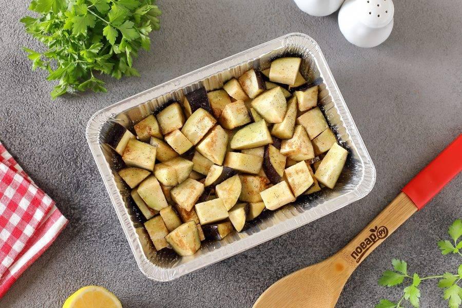 Форму для запекания смажьте маслом и выложите в один слой нарезанные кубиками баклажаны. Баклажаны посолите, поперчите и сбрызните растительным маслом. Если хотите, чтобы баклажаны получились максимально нежные, то лучше их предварительно обжарить.