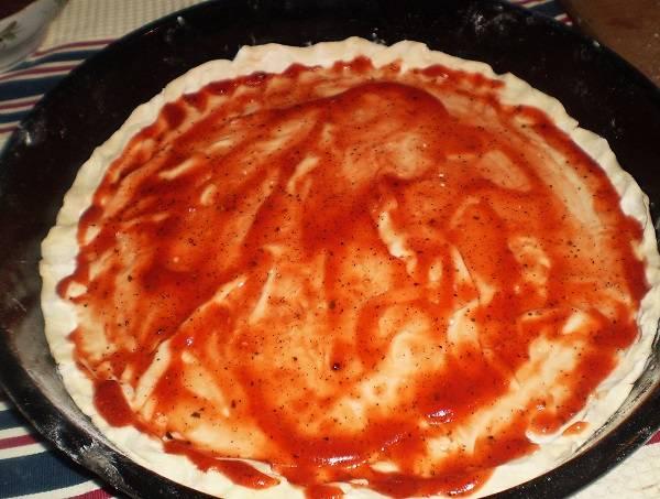 6. Лист слоеного теста или специальную основу для пиццы смазать соусом. При желании можно присыпать немного также сыром.