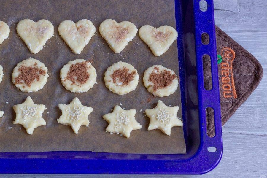 Выложите заготовки на противень, застеленный пекарской бумагой и посыпьте кунжутом, корицей, корицей с сахаром или просто сахаром. Поставьте печенье в разогретую до 180 градусов духовку на 15-30 минут до румяности. Время выпечки зависит от размера и толщины печенья.