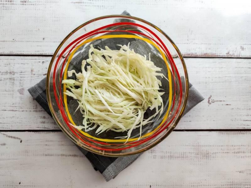 Капусту мелко нарежьте и выложите в глубокую емкость, чтобы в конце было удобно перемешивать салат.