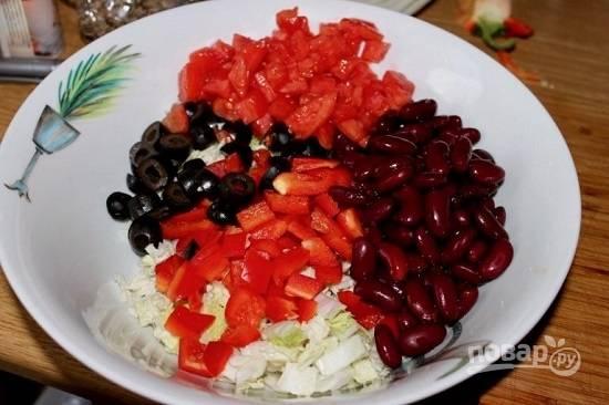 В миску выкладываем консервированную фасоль,  нарезанную соломкой капусту. Перец и помидор нарежем кубиками, оливки нарежем кружочками.