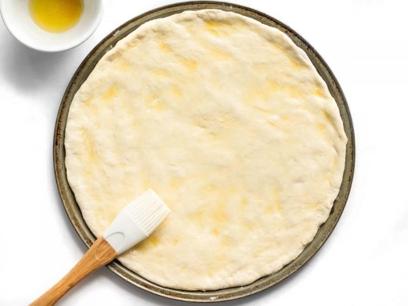 5.Выложите на противень тесто. Перемешайте чесночно-оливковую смесь и нанесите ее на тесто.