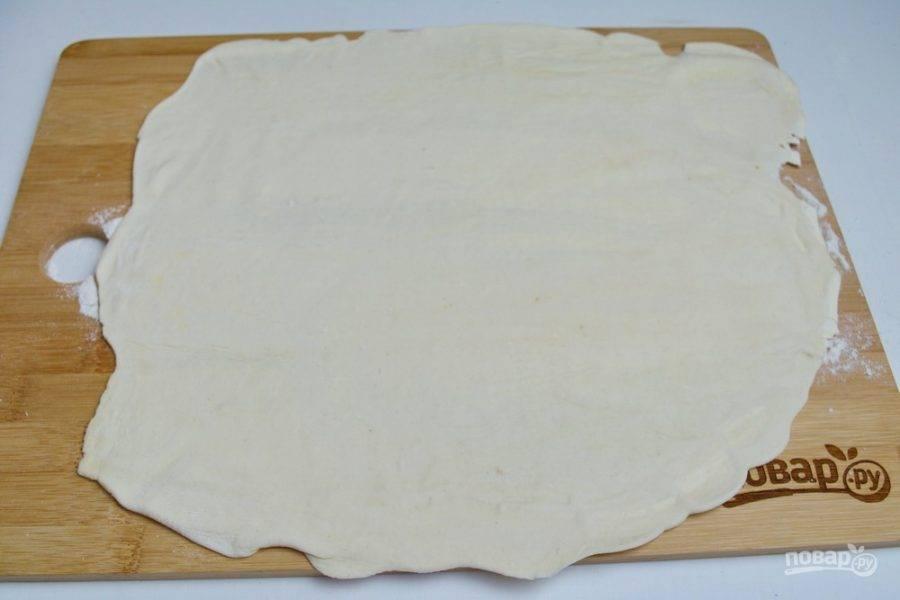 Доску присыпьте немного мукой, по центру выложите тесто и раскатайте его в тончайший пласт, но не до дыр.