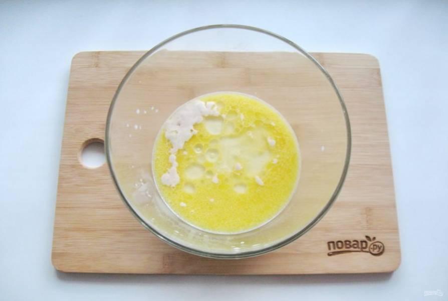 Растопите сливочное масло, немного охладите и добавьте к молоку с дрожжами.
