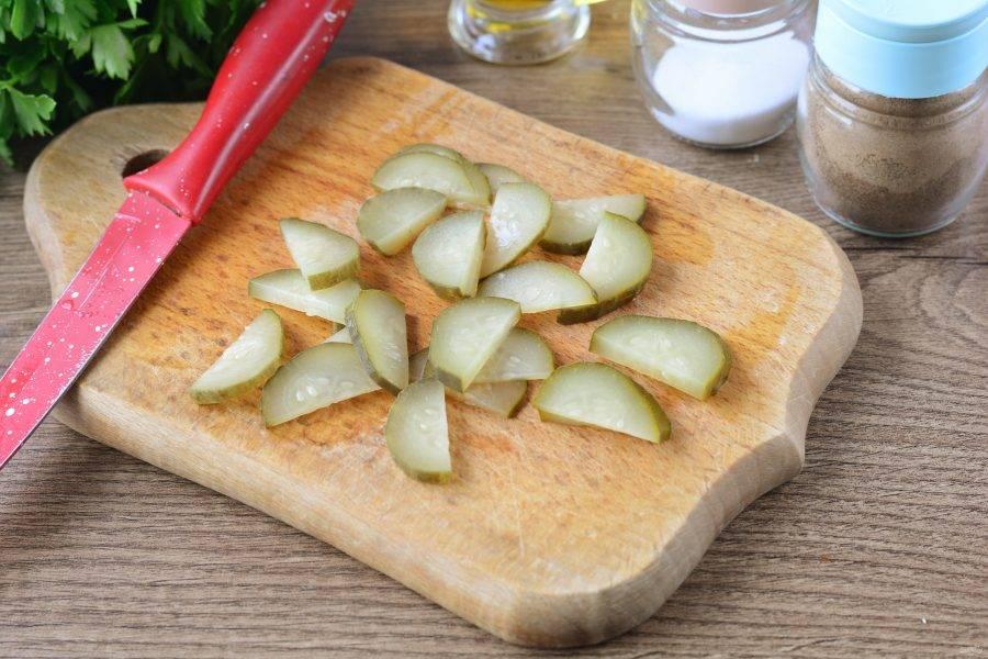 Нарежьте соленые огурцы тонкими полукольцами.
