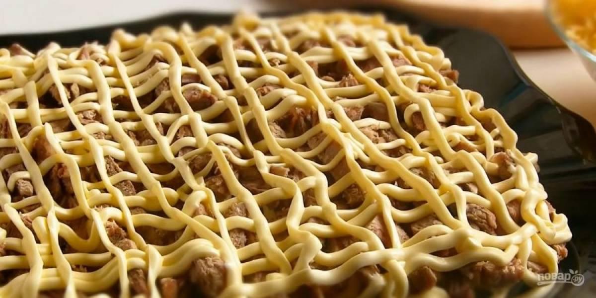 3.  Сверху нарисуйте сеточку из майонеза. Затем выложите слой мяса и майонез, потом — яйца и майонез. В конце выложите сыр и украсьте салат зеленью или майонезом. Приятного аппетита!