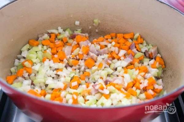 2.Добавьте к бекону морковь, сельдерей, лук, уменьшите огонь и готовьте все около 15 минут. Добавьте пропущенные через пресс чеснок и готовьте пару минут.