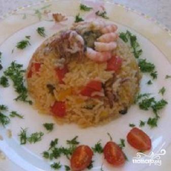 5.Рис с морепродуктами выкладываем на тарелку. украсить зеленью и дольками помидора.