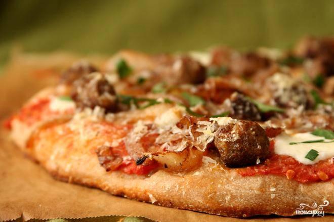 3. Выпекать 8-10 минут, пока сыр не начнет бурлить и не станет коричневым. Достать пиццу из духовки, посыпать половиной измельченной петрушки и дать остыть на решетке примерно 5 минут до нарезки и подачи. Повторить с оставшимся тестом и начинкой, чтобы приготовить вторую пиццу.