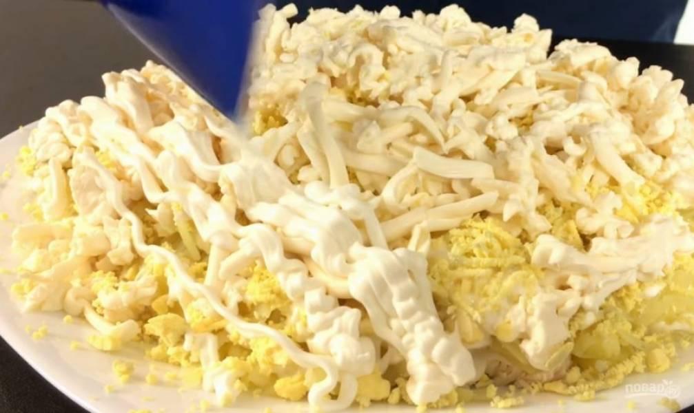 Сырок предварительно лучше отправить в морозилку на один час. Натрите его на терке. И сверху — майонез.
