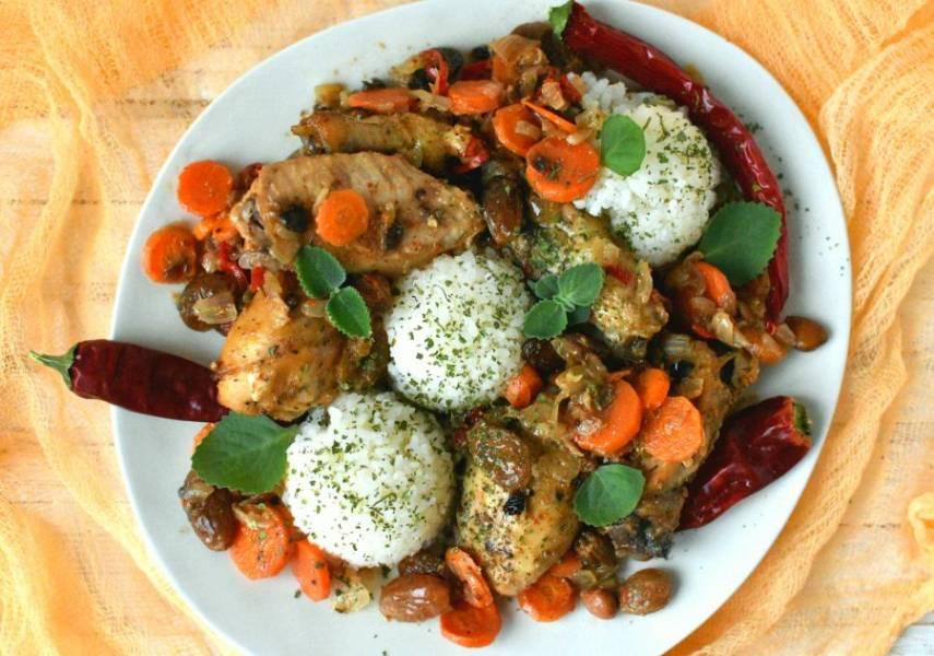 Сервируйте курицу горячей, с рассыпчатым рисом, заправленным топленым маслом, на гарнир. Украсьте блюдо свежей мятой и кинзой.