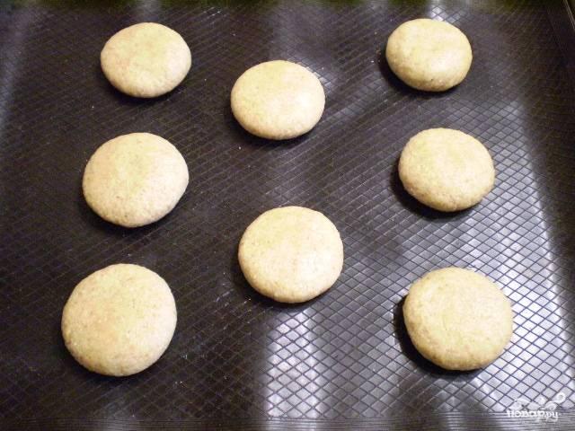 7. Теперь разделите его на 8 частей. Скатайте их в шарики и слегка приплюсните руками. Выложите их на силиконовый коврик или на бумагу для выпечки. Отправьте в разогретую до 180 градусов духовку на 20 минут.