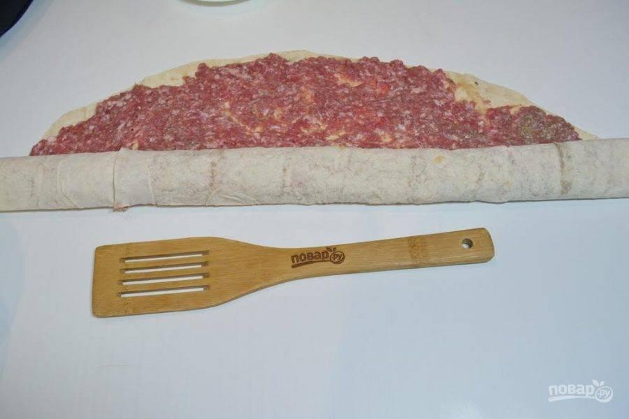 3. Дайте лавашу с фаршем просто полежать на столе. Фарш пропитает мясным соком лаваша и при сворачивании лаваш не будет рваться. Сверните лаваш в рулет.