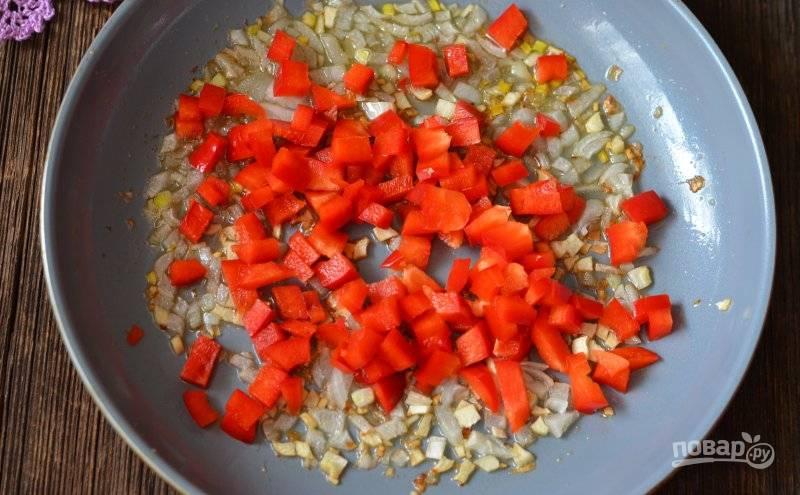 В сковороду добавьте нарезанный перец. Перемешайте овощи. Обжарьте их в течение 2-х минут.