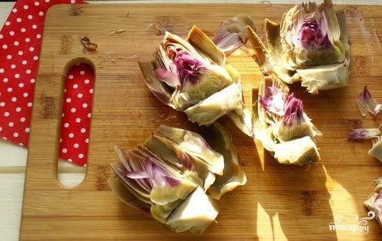 Теперь разделайте артишок. Разрежьте его на четыре одинаковые части, удалите сердцевину, которую не употребляют в пищу. Дайте овощу остыть.