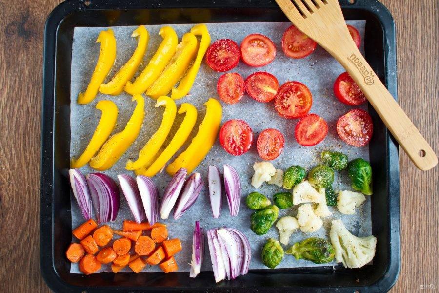 Овощи нарежьте: перец - толстыми ломтиками, помидоры черри - пополам, лук - дольками, морковь - крупными кружками. Посолите, поперчите по вкусу, посыпьте сушеным чесноком, сбрызните оливковым маслом. Поставьте запекаться в разогретую до 200 ºC духовку на 15 минут.
