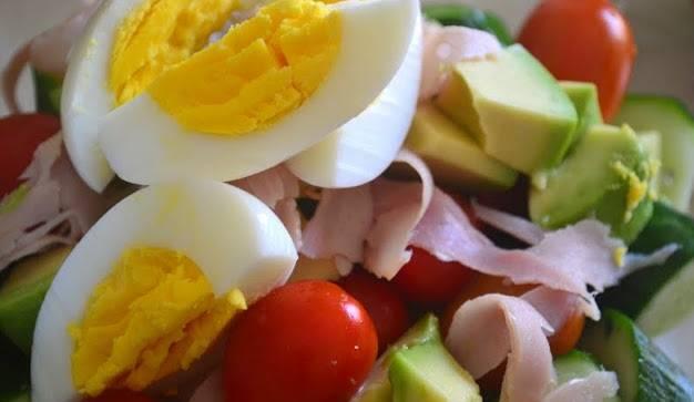 1. Яйца отварите вкрутую, остудите и порежьте на 4 части вдоль. Отварить яйца можно накануне. Ветчину нарежьте кубиками или полосками. Помидорки промойте и просушите. Огурцы промойте и нарежьте косыми кружками. Используйте авокадо или пучок любимого салата. Салат надо промыть и посушить, можно порвать руками, а авокадо порежьте кубиками. Все ингредиенты смешайте в большой миске.