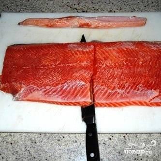 Выкладываем кусок филе на ровную поверхность, делаем косой надрез и, максимально прижимая лезвие ножа к шкуре рыбы, отделяем филе от шкуры.
