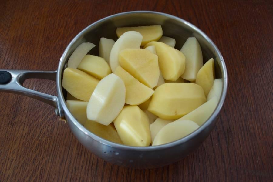 Для начала поставим вариться картофель. Для этого его следует очистить. Каждый разрезать на 4 части. Сложить в кастрюлю. Залить водой. Довести до кипения. Кипящий картофель посолить и варить до готовности.