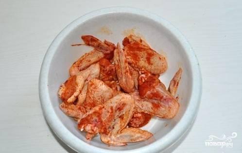 Выкладываем подготовленные крылышки в миску, посыпаем смесью соли, перца и карри. Можно добавить острого красного перца. Хорошо перемешиваем, чтобы все крылышки равномерно покрылись специями.