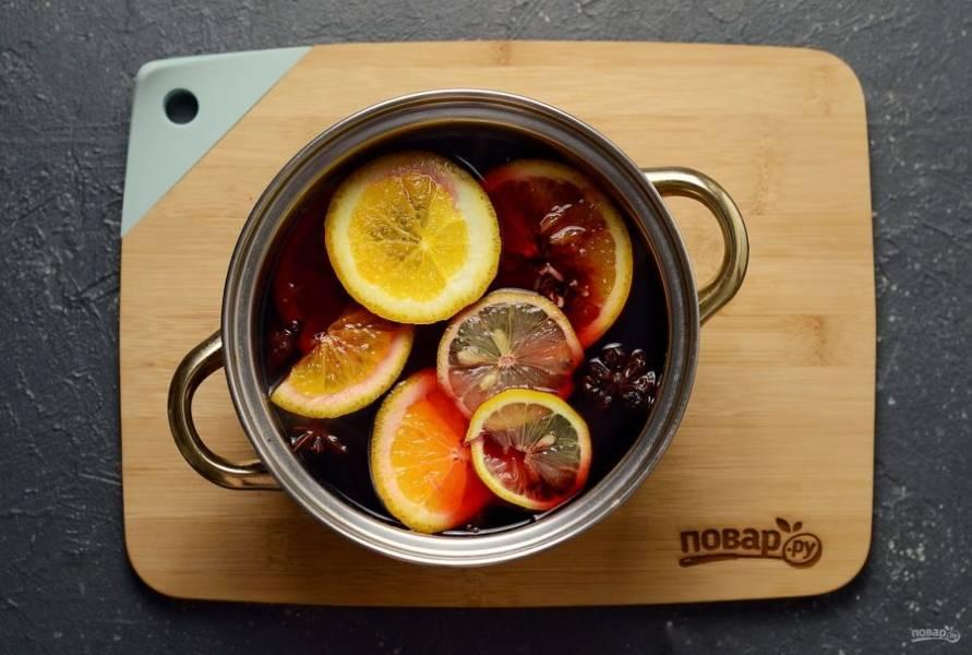 Затем добавьте нарезанный кружочками апельсин и лимон. Добавьте сахар. Варите еще 5-6 минут.