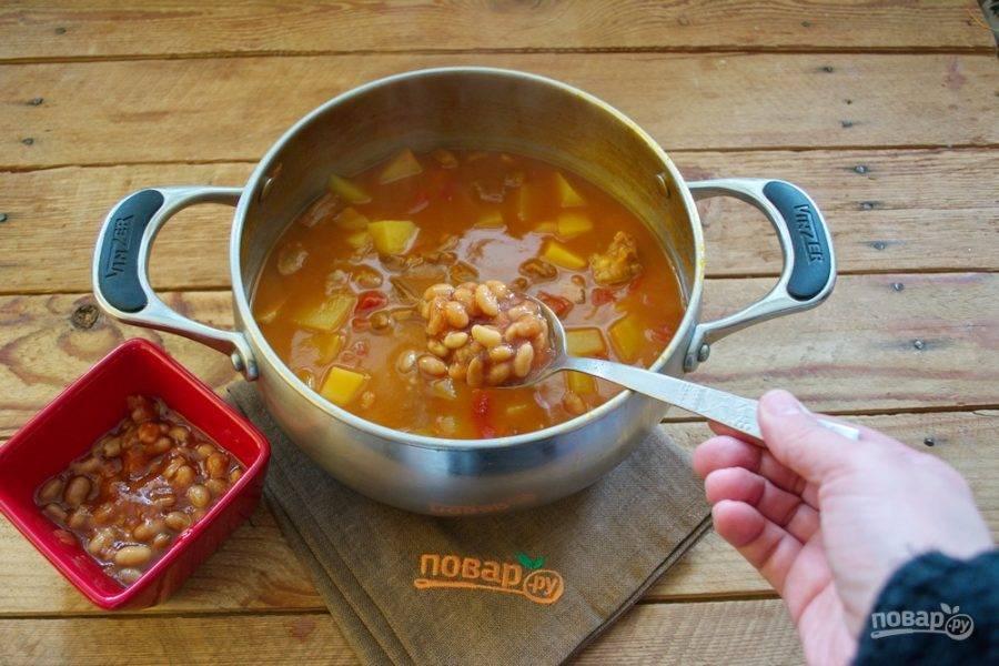 В конце варки картофель должен стать мягким, жидкость немного уварится. Добавьте в суп консервированную фасоль вместе с соусом. Фасоль можно приготовить в домашних условиях отдельно. Если будете готовить фасоль, то уместнее будет взять несколько видов (красную и белую).
