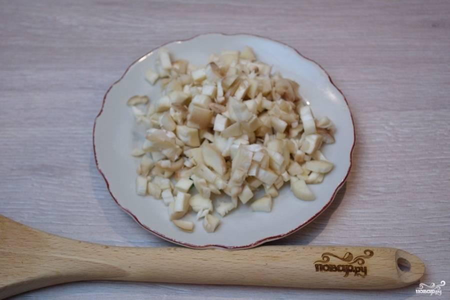 Шляпки грибов отложите. Посолите их и поперчите по вкусу. Отставьте. Отделенные ножки нужно нарезать на мелкие кубики. Резать нужно мелко, чтобы начинка из шляпок не вываливалась.