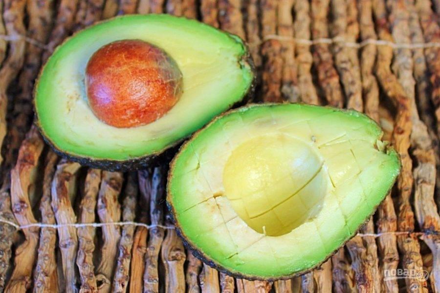Авокадо разрезаем на две части. Половину авокадо режем кубиком, не вынимая мякоть из шкурки.