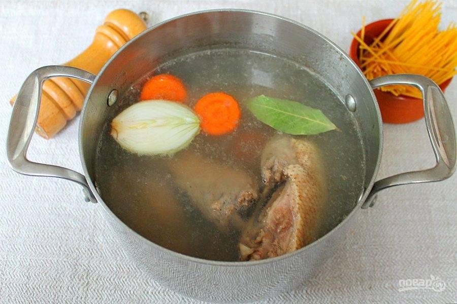 2. Утиное мясо промываем и кладем в холодную воду. Доводим до кипения и убираем пену. Добавляем соль, лавровый лист, половину луковицы и немного моркови. Бульон варим около часа.