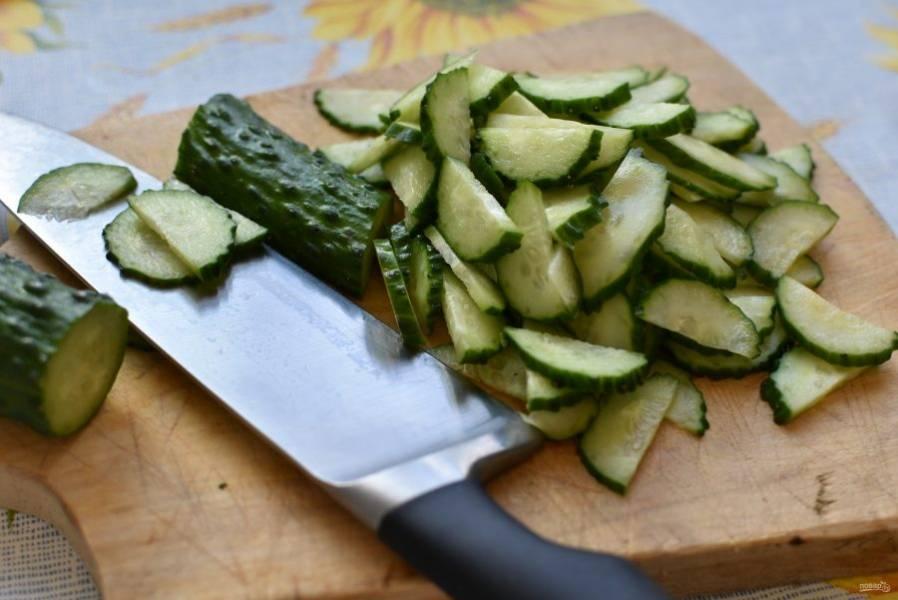 Продукты должны быть охлажденными,  тогда салат будет вкуснее. Промытые и обсушенные огурцы разрежьте вдоль и нарежьте  тонкими ломтиками. Выложите в просторную миску.