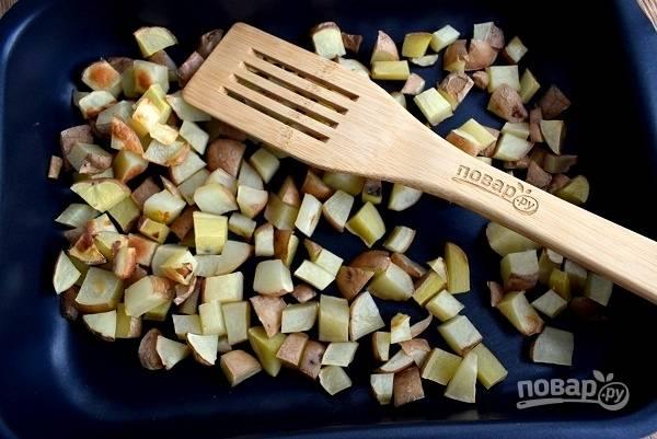 Картофель нарежьте на кубики, посолите, поперчите, выложите на противень и запекайте в разогретой духовке в течение 35 минут.