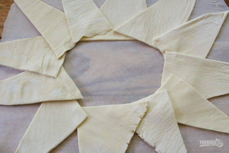 Раскатанное тесто нарежьте на треугольники. По кругу выложите их на пергаменте. Так будет удобнее сформированный пирог и перенести на противень. Итак, тесто выложили.