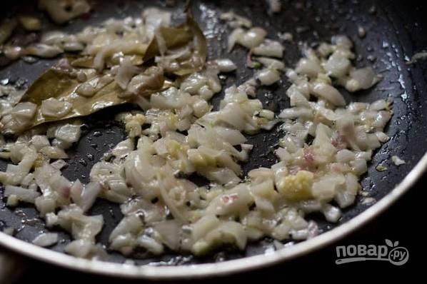 Чеснок и лук измельчите, в глубокой сковороде растопите масло и обжарьте эти овощи до золотистости с лавровым листом.