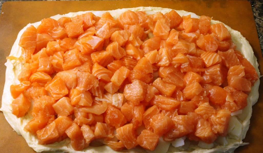 Большую часть раскатайте и выложите в форму для выпекания. Сверху слоями (картофель, лук, рыба) выложите начинку.