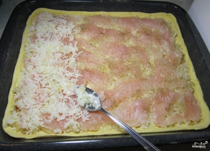 Раскатайте тесто в тонкий слой, чтобы оно полностью покрывало противень. Смажьте противень и выложите раскатанное тесто. Смешайте рис с луком, посолите по вкусу и выложите тонким слоем по всему противню. Поверх выложите нарезанные кусочки рыбы, приправьте солью и перцем по вкусу. Под рыбу положите лавровый лист, расположите его в разных местах. Поверх рыбы снова распространите слой риса.
