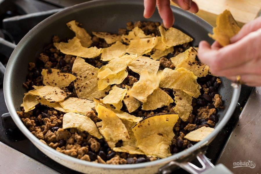 4. Добавьте в фарш фасоль, сальсу и измельченный перец чили. Поломайте лаваш на кусочки и добавьте к фаршу.