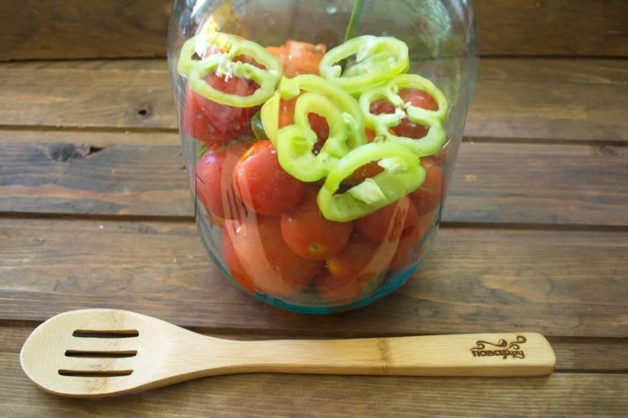 Наполните половину банки помидорами. Нарежьте болгарский перец и уложите туда же. Также добавьте в банку пару измельченных зубчиков чеснока.