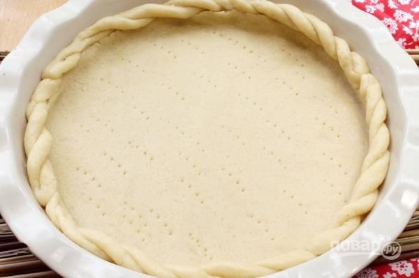 Готовое тесто уложите в форму для выпечки. Сделайте бортики. Можете свернуть тесто в корзинку. Проткните дно вилкой по всей площади.