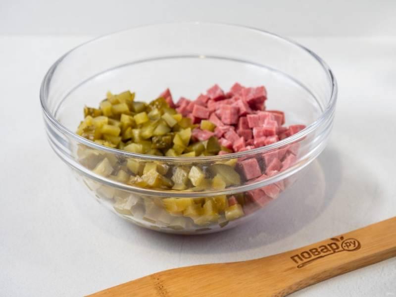 Колбасу и огурцы нарежьте небольшими кубиками.