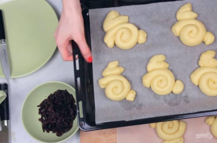 5. Выложите булочки на застеленный пергаментной бумагой противень. В оставшийся желток добавьте столовую ложку молока и перемешайте. Смажьте булочки желтком и прикрепите глаза кроликам (изюм). Посыпьте булочки сахаром.