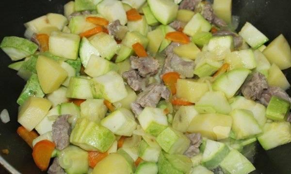 Добавляем картофель и кабачки, порезанные кубиками. Для остроты добавляем измельченный чеснок. Продолжаем готовить.
