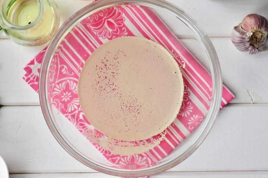 Влейте теплую воду в миску, добавьте дрожжи.