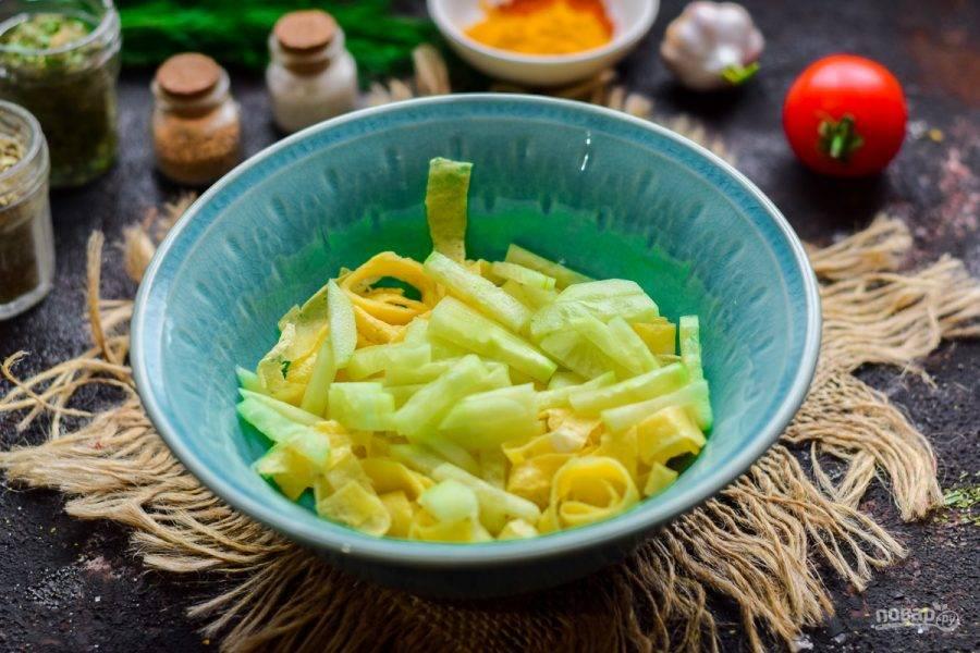 Переложите блинную нарезку в салатник, добавьте нарезанный кусочками свежий огурец.
