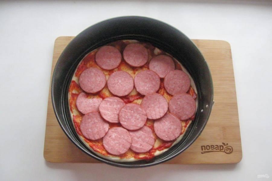 Выложите на тесто нарезанную колбасу.