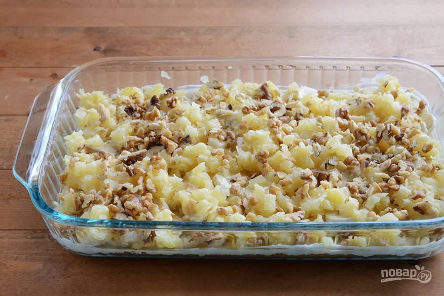 Далее измельчите орехи. Рассыпьте часть на ананас.