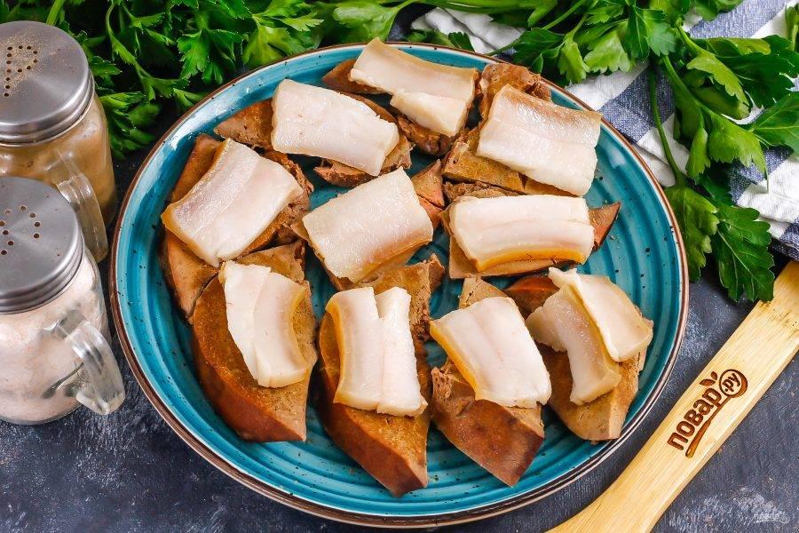Нарежьте отварное сало и выложите ломтики сала на печеночные ломтики.